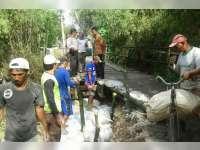 Bersama Warga, Bhabinkamtibmas Desa Klepek Sukosewu Perbaiki Tanggul Jembatan